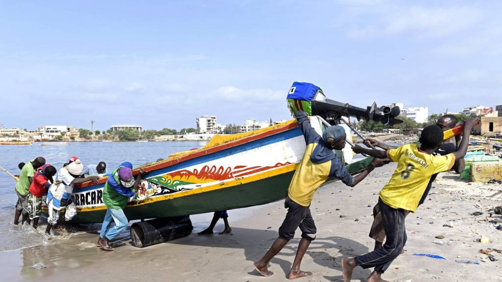 Young fishermen pull a wooden pirogue to the shore of the traditional fishing harbour of Soumbedioune in Dakar, on July 2, 2015.