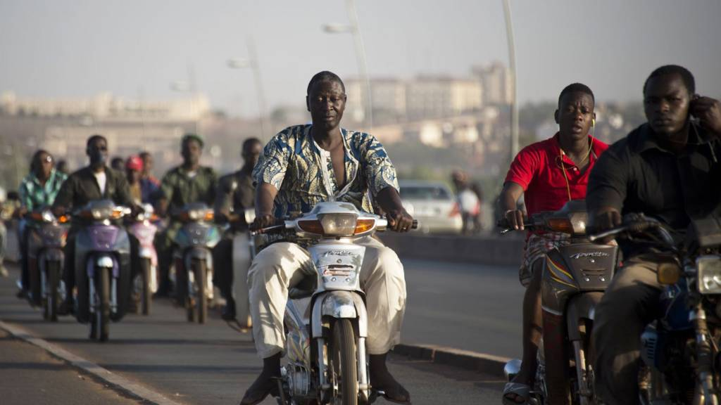 People riding over a bridge in Mali's capital, Bamako - archive shot