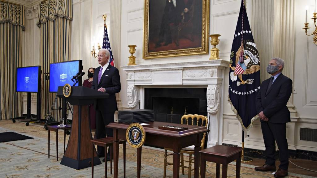 President Joe Biden speaks as US Vice President Kamala Harris, left, and Anthony Fauci, director of the National Institute of Allergy and Infectious Diseases, right, listen during an event on his administration's Covid-19 response in the State Dining Room of the White House in Washington, DC, USA, on 21 January 2021