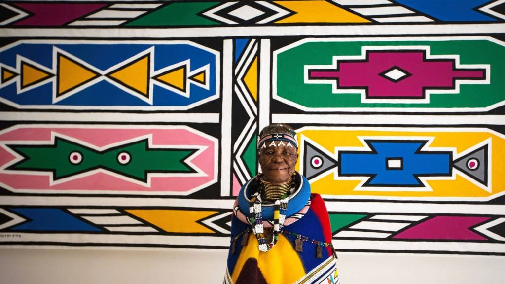 South African artist Esther Mahlangu stands in front of one of her piece
