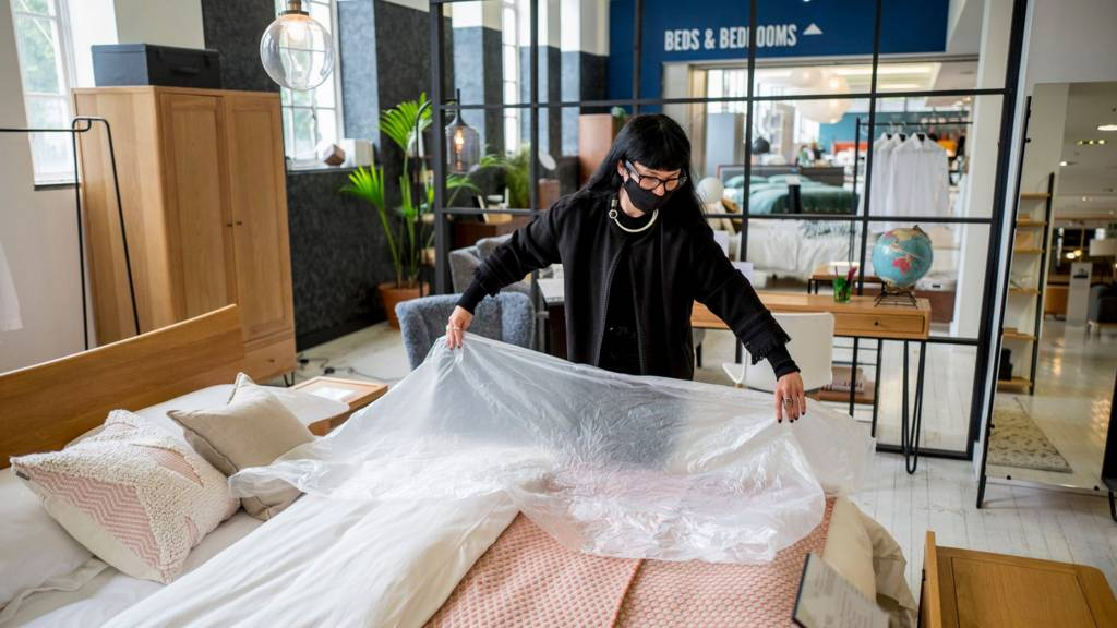 A member of staff wearing PPE (personal protective equipment), including a face mask as a precautionary measure against COVID-19, demonstrates the use of plastic film for customers to test beds, at the re-opened Heal's flagship store in central London on June 8, 2020