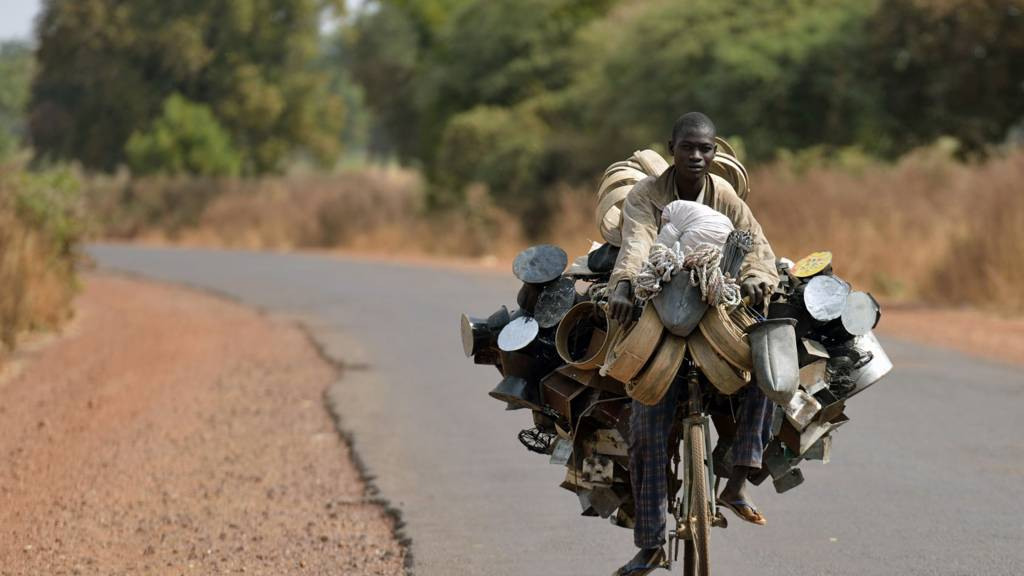 A man on a bicycle loaded with pots in Mali
