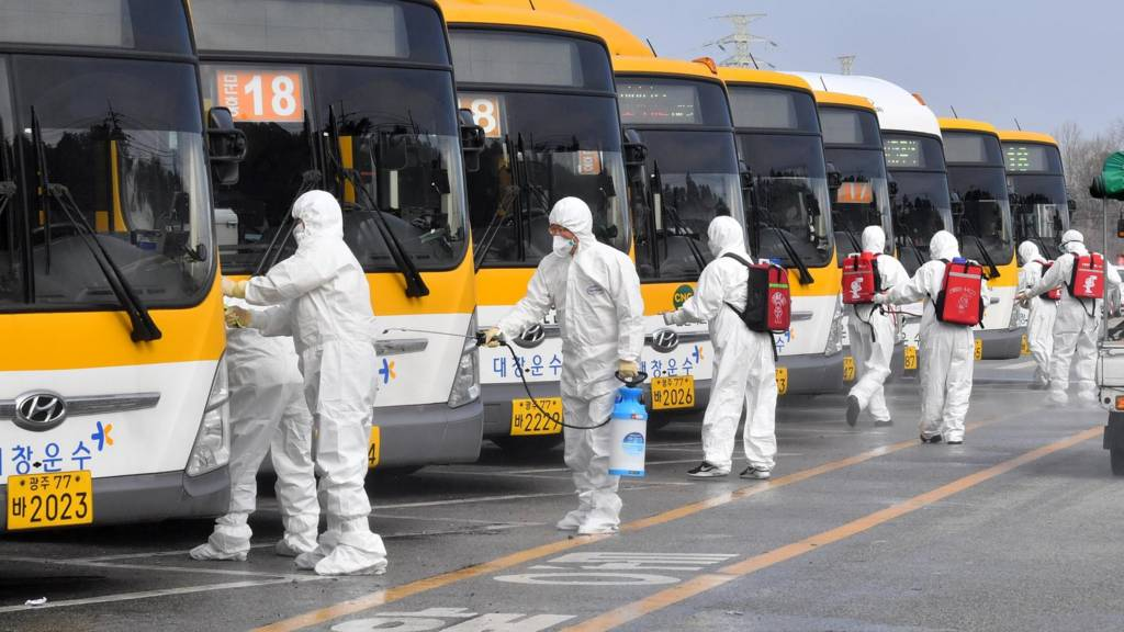 South Korean workers disinfect buses
