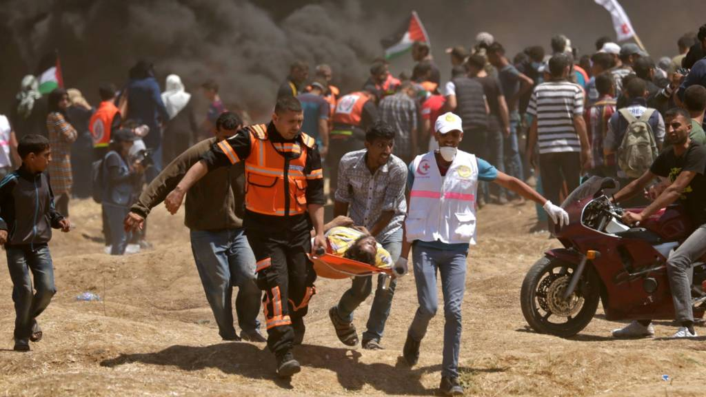 Palestinians carry a person wounded during a protest on the Israel-Gaza border (14 May 2018)