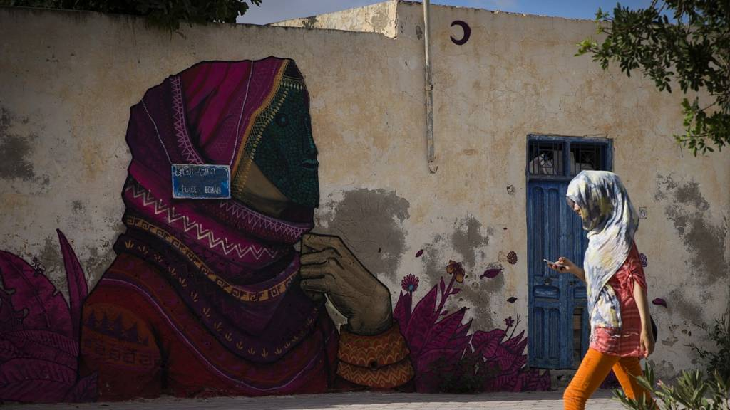A woman walks past a mural by Mexican artist SANER in the village of Erriadh, on the Tunisian island of Djerba.