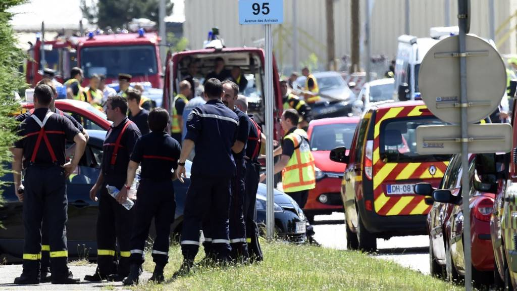 French police and firefighters gather at the entrance of the Air Products company in Saint-Quentin-Fallavier, near Lyon