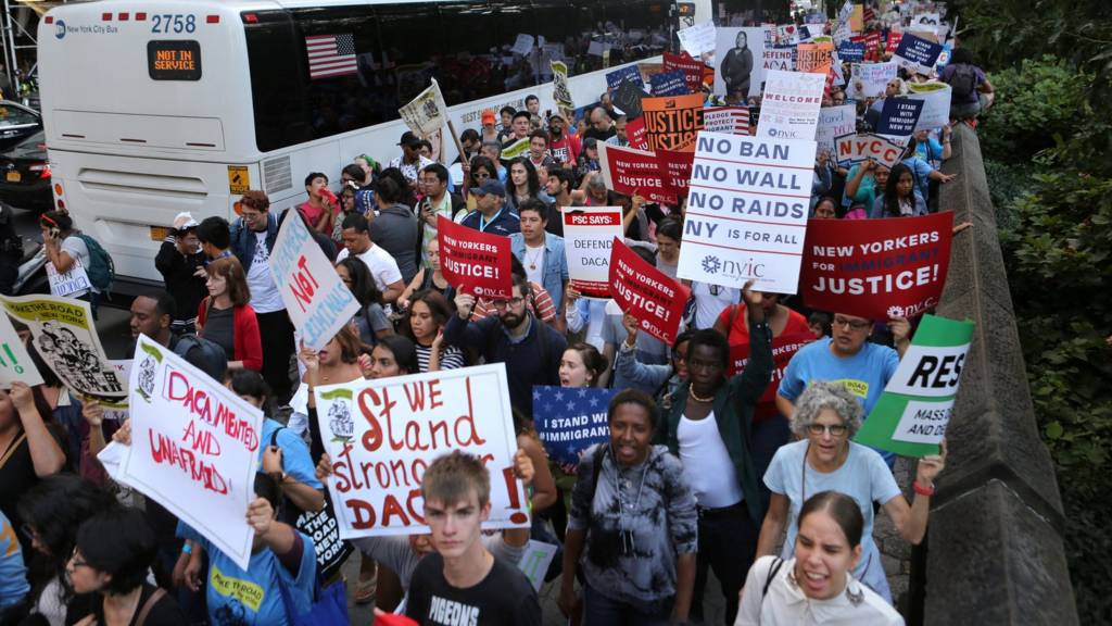 """People march and chant slogans against U.S. President Donald Trump""""s proposed end of the"""