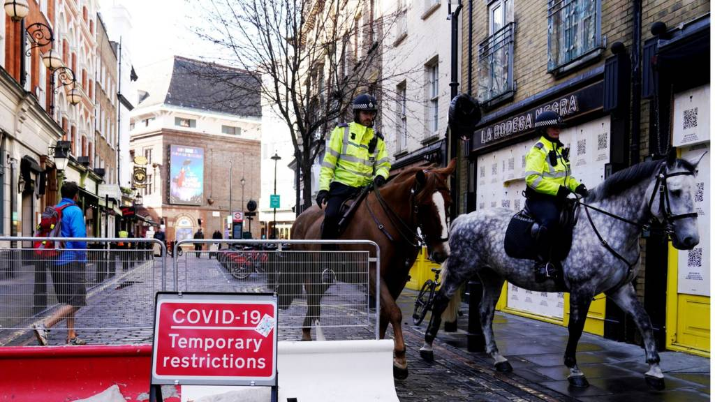 Police horses pass Covid sign in central London