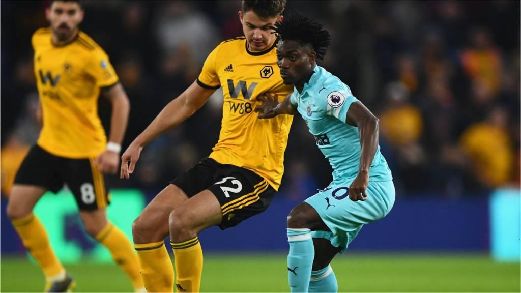 Christian Atsu of Newcastle United holds off Leander Dendoncker