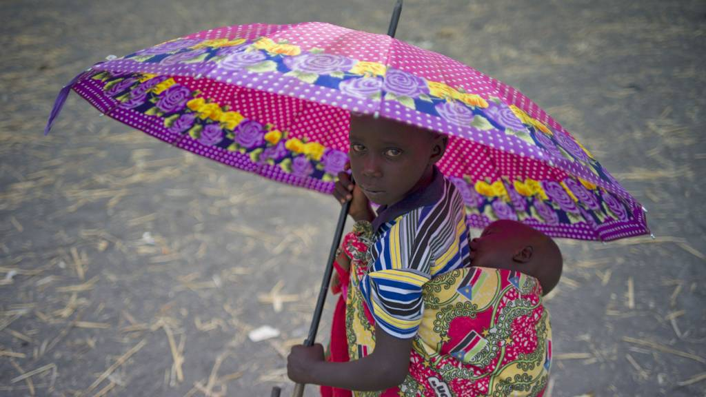 A refugee child from South Sudan with a baby on her back holding an umbrella in Uganda - 2017
