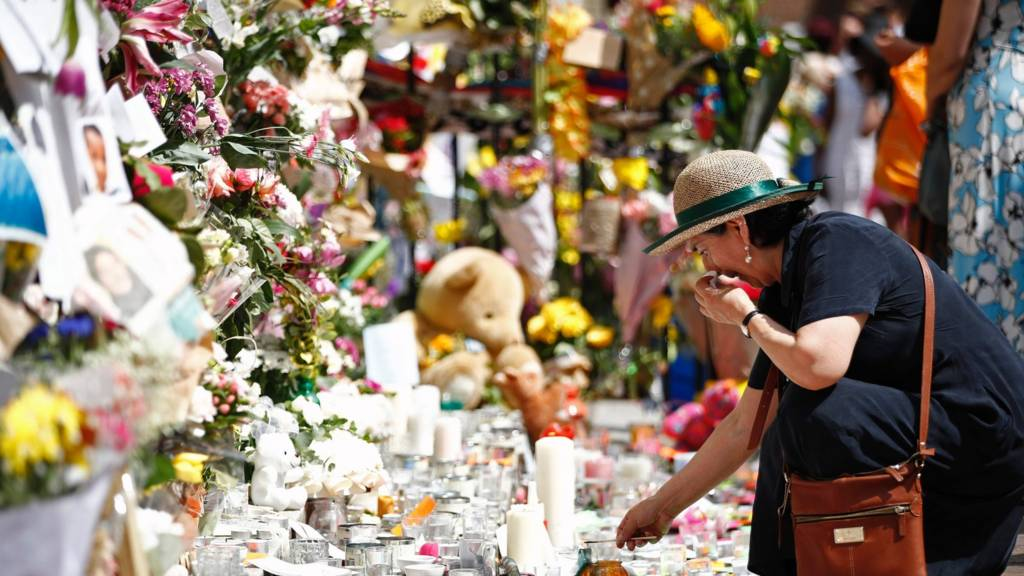A woman lays flowers in tribute to the victims of the June 14 Grenfell Tower block fire in Kensington, west London, 17 June