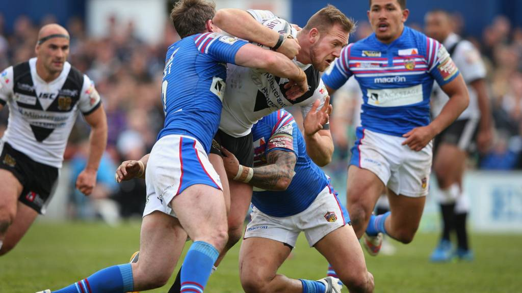 Liam Watts of Hull FC is tackled by Matty Ashurst and Tinirau Arona of Wakefield Wildcats