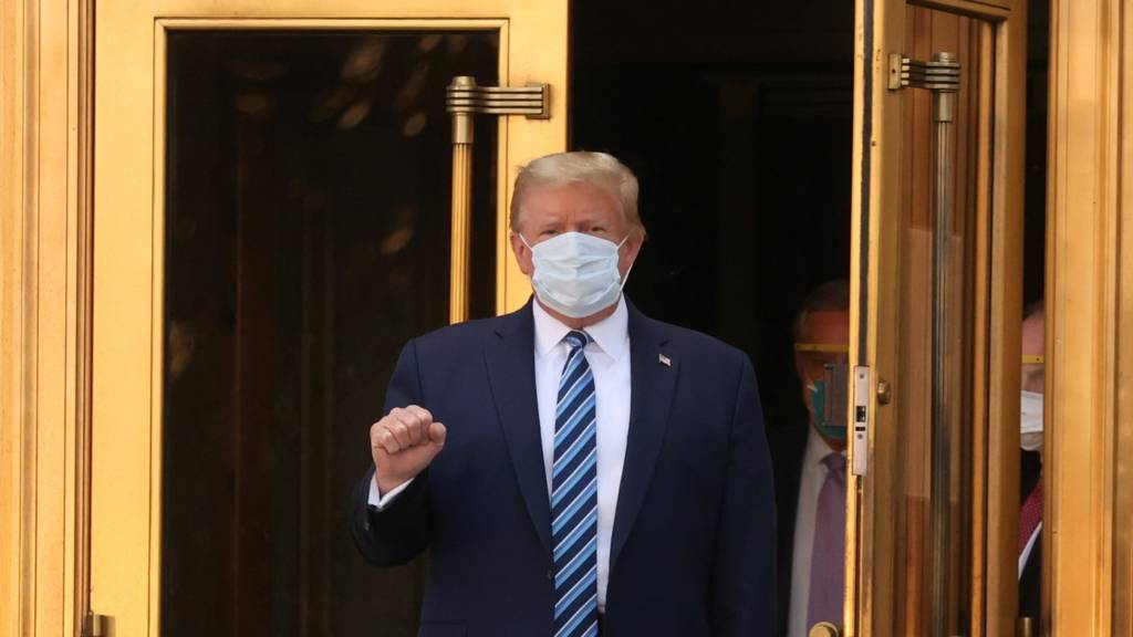 US President Donald Trump makes a fist as he walks leaves Walter Reed National Military Medical Center