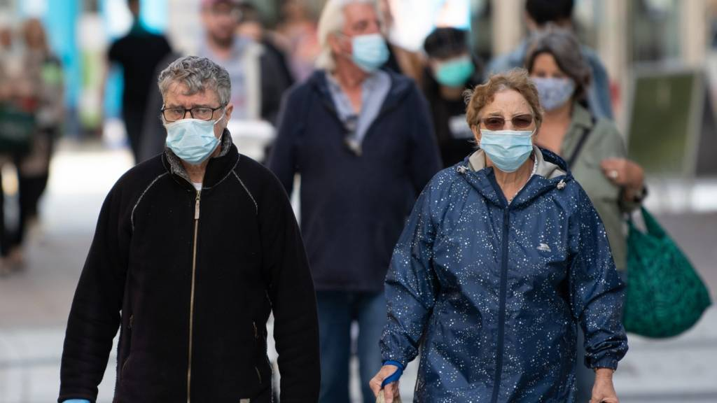A man and woman wear surgical face masks on Queen Street in Cardiff