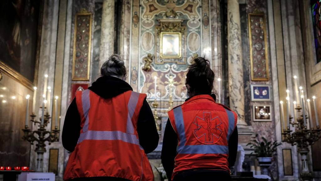 Emergency services personnel pause for a prayer in the Church of Santa Rita da Cascia alle Vergini, Rome, Italy, 27 March 2020