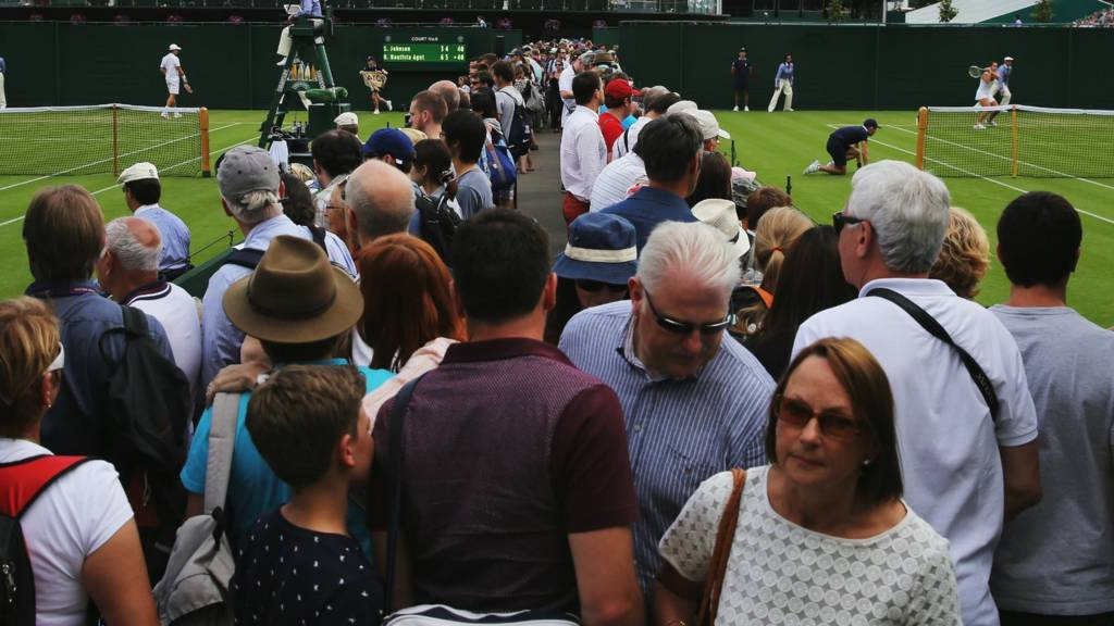 Spectators move about the outside courts