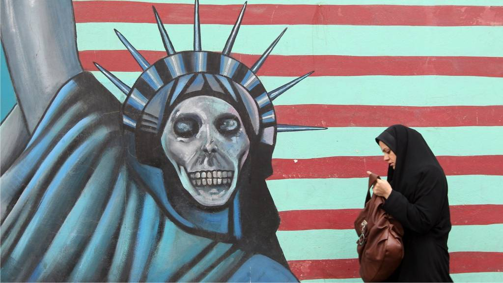 An Iranian woman walks past an anti-US mural painted on the wall of the former US embassy in Tehran in November 2011