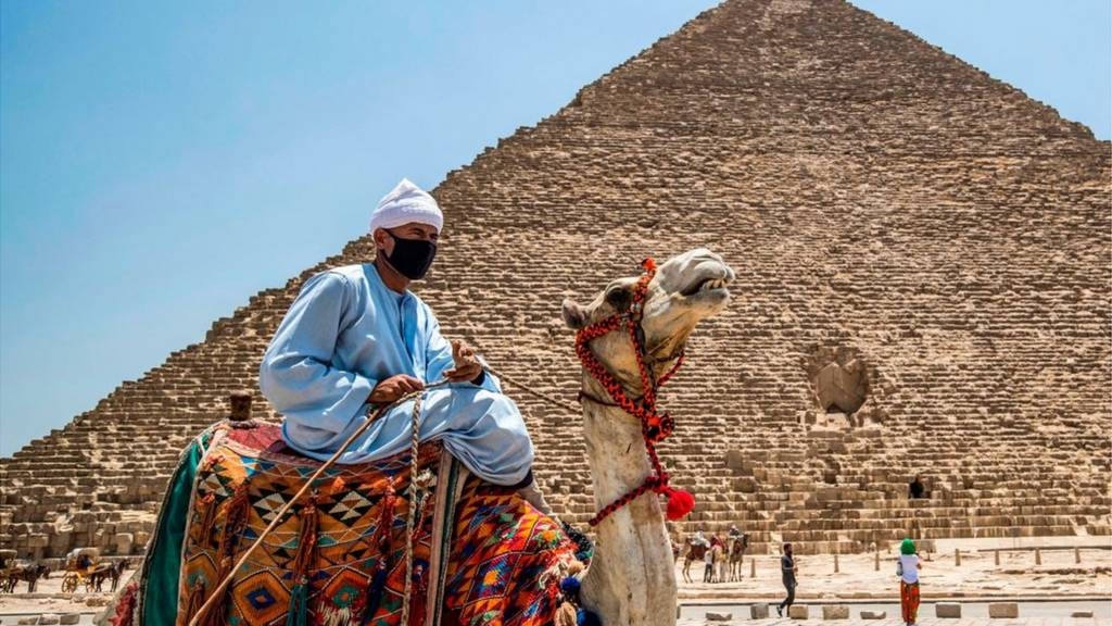 A man rides a camel past the pyramids