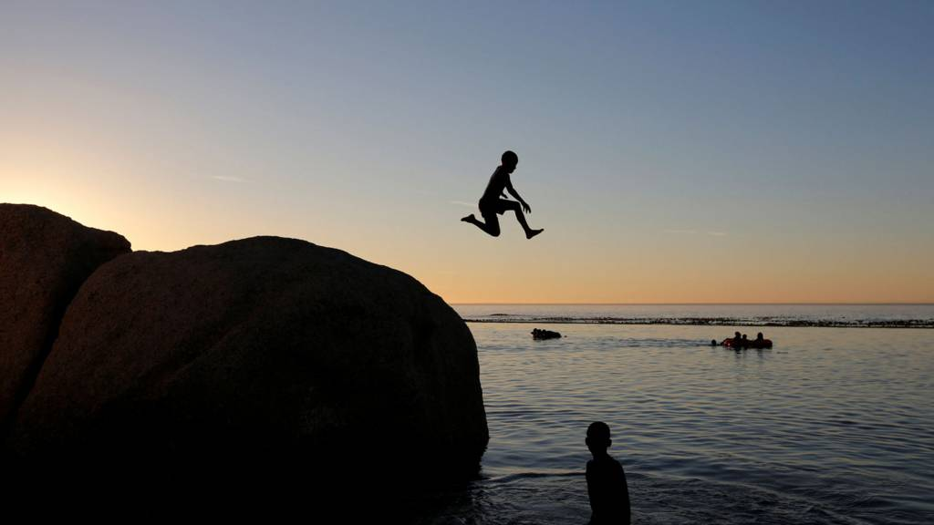 A child leaps leaps into a tidal pool as temperatures soar at Camps Bay beach in Cape Town, South Africa - 11 December 2016