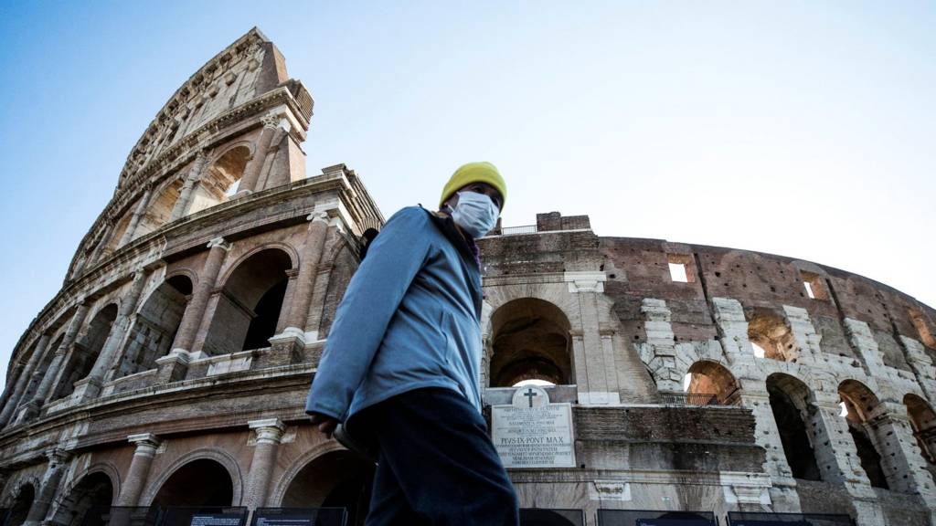 Tourist walks outside colosseum