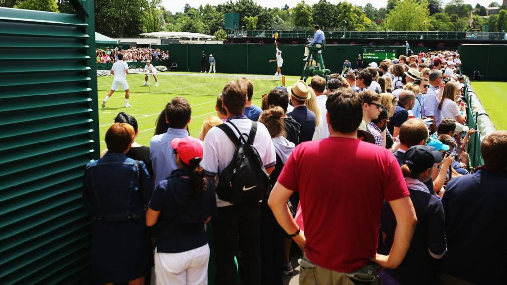 Fans walk around the outer Wimbledon courts
