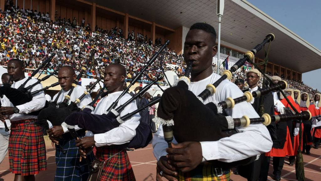 Musicians playing the bagpipes lead the Gambian court as they parade during the inauguration ceremony for the start of Barrow's presidency at the Independence Stadium in Bakau