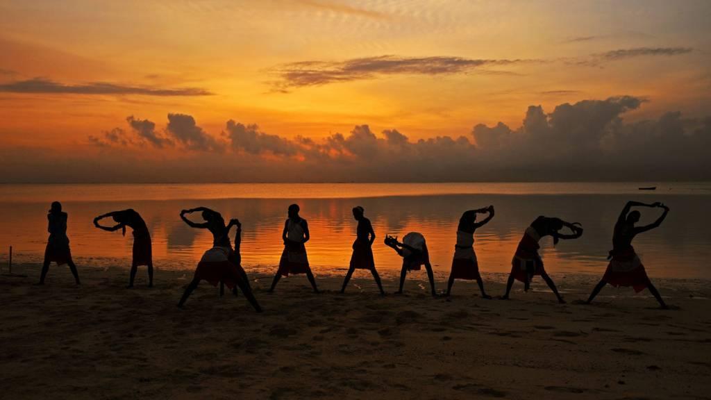 Maasai cricketers exercising on a beach in Mombasa, Kenya