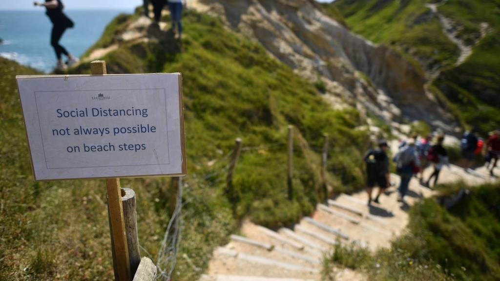 People pass a sign warning that social distancing may not be possible on the beach steps leading to the popular tourist spot Durdle Door near West Lulworth on the south coast of England on Sunday