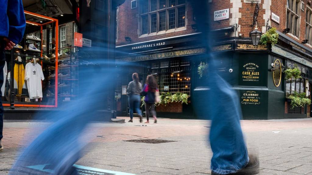 Man walks in street outside pub