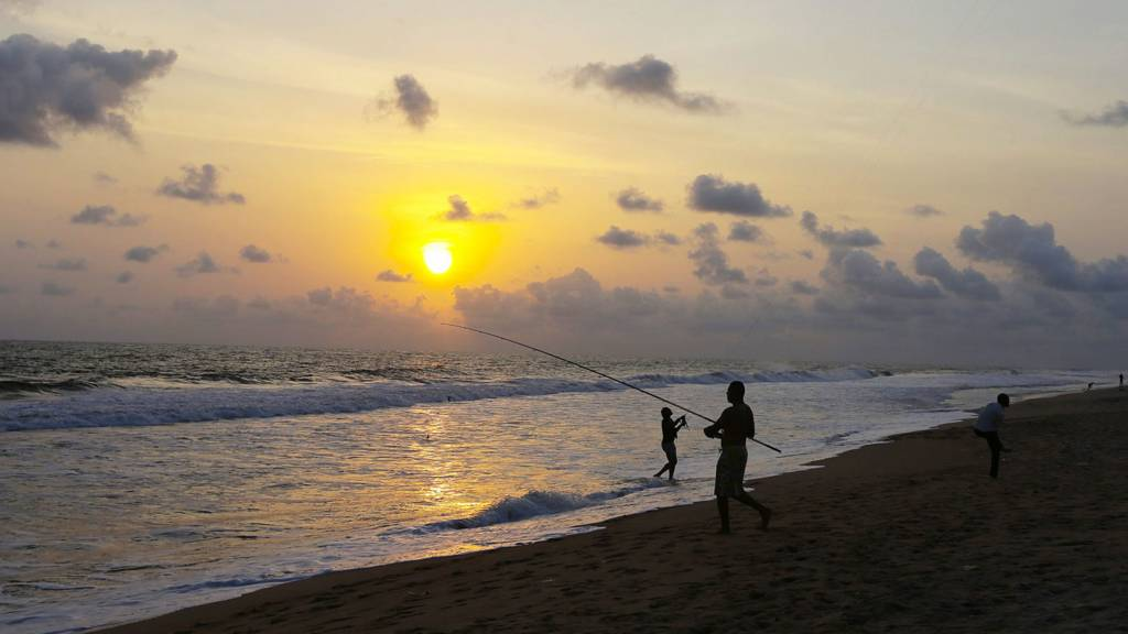 Fishermen at sunset on a beach in Grand Bassam, Ivory Coast - November 2016
