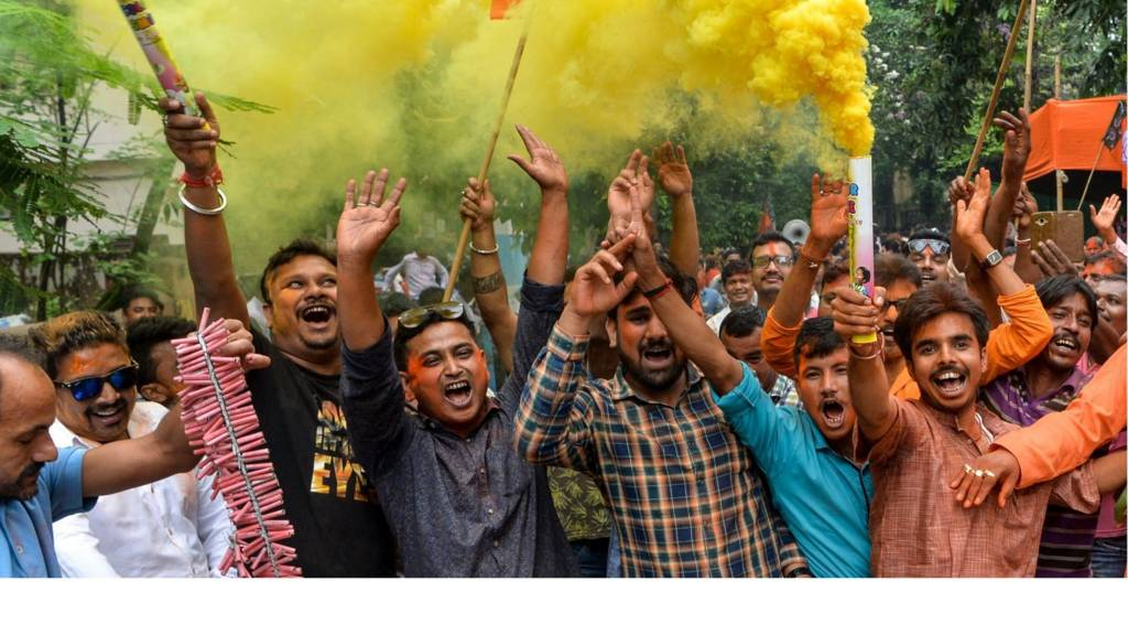 "Indian supporters of Bharatiya Janata Party (BJP) hold colour smoke crackers as htey celebrate on the vote results day for India""s general election in Siliguri on May 23, 2019. -"
