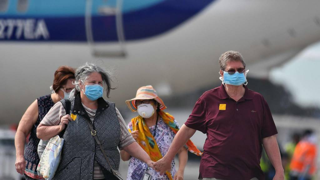 Passengers disembarking from plane in masks