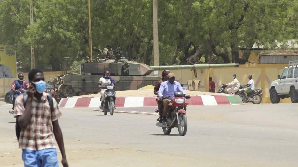 People walk and drive past a tank in Chad's capital N'Djamena