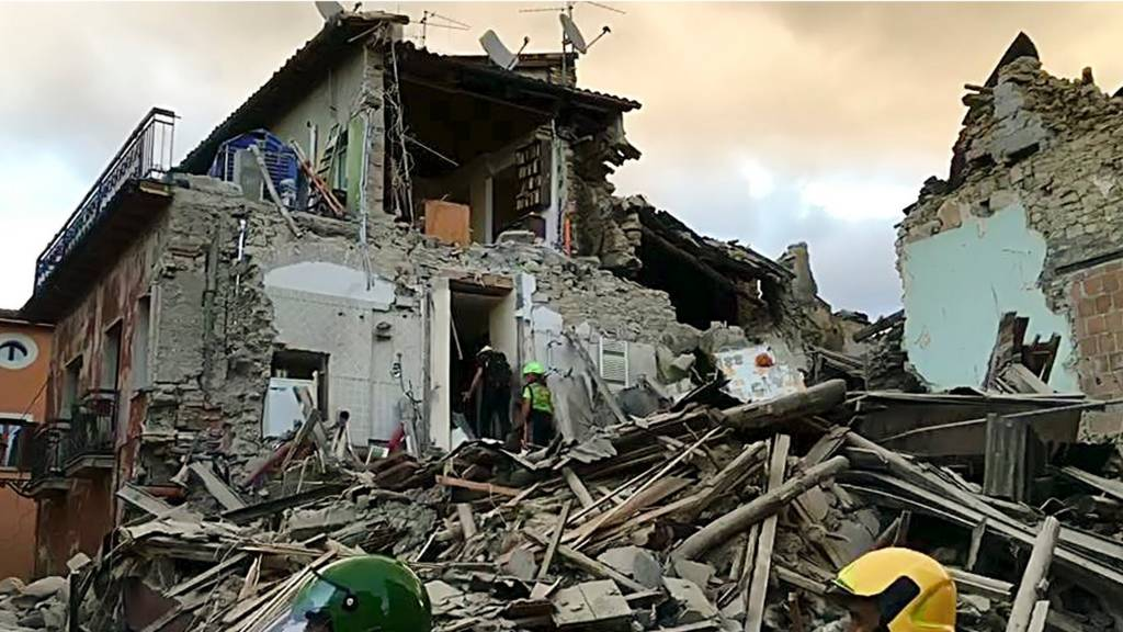 Rescuers searching a collapsed building in Amatrice,