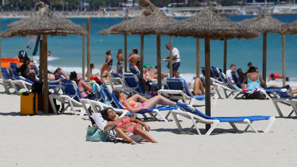 People sunbathe in Magaluf beach