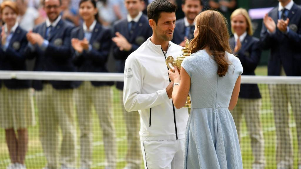Novak Djokovic accepts the trophy from the Duchess of Cambridge
