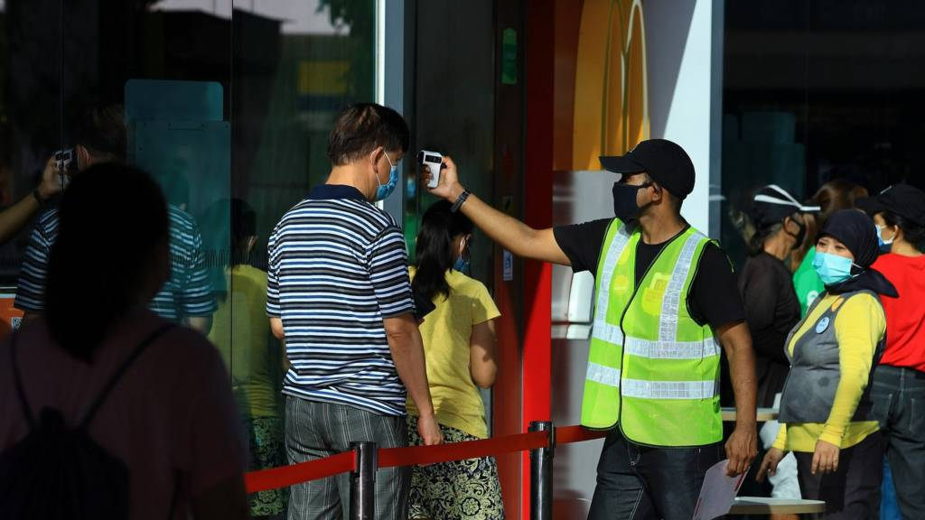 People get their temperature checked to enter a market in Singapore
