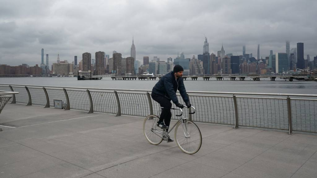 Man cycling with Manhattan in background