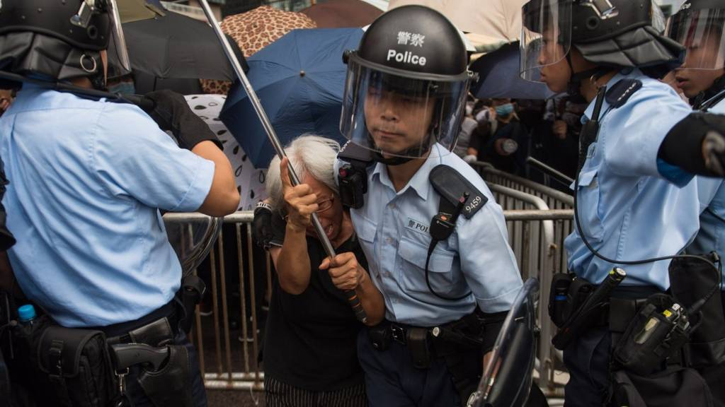 A police officer takes a protester away from a demonstration site during a rally against an extradition bill outside the Legislative Council in Hong Kong