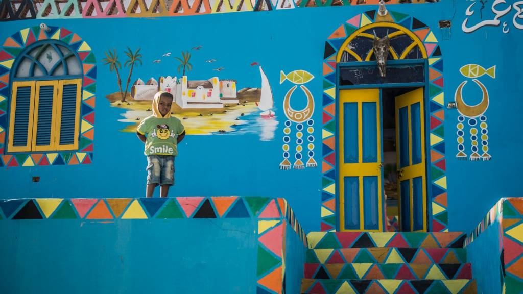 A boy stands in front of a painted house