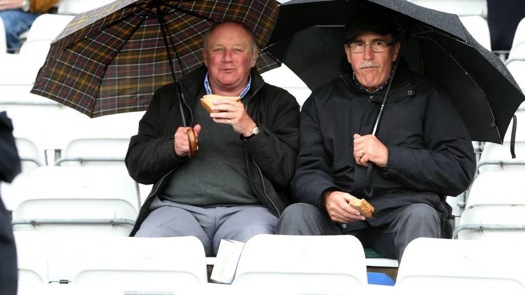 Fans eat snacks in the rain