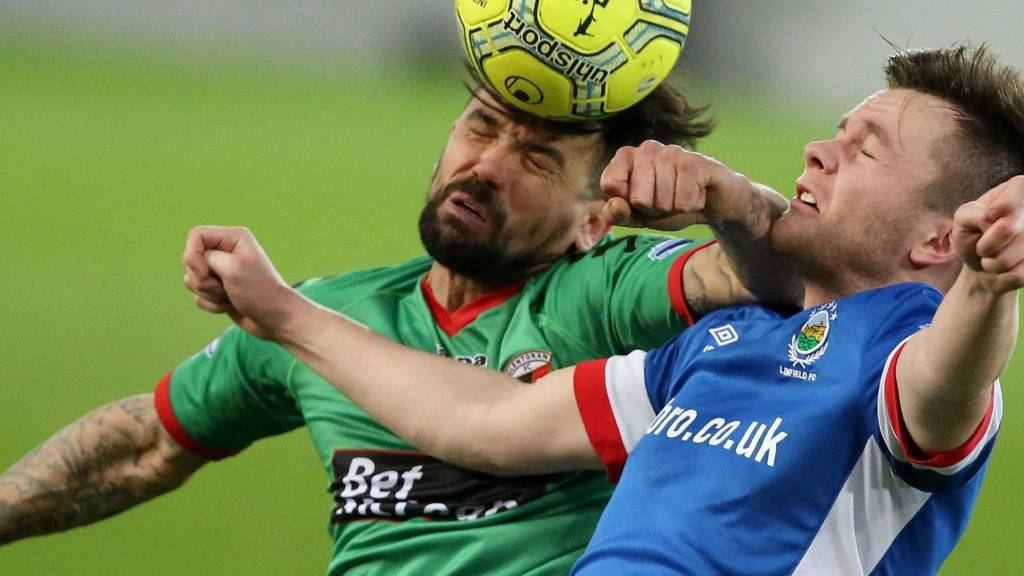 Glentoran striker Nacho Novo beats Linfield's Niall Quinn to the high ball