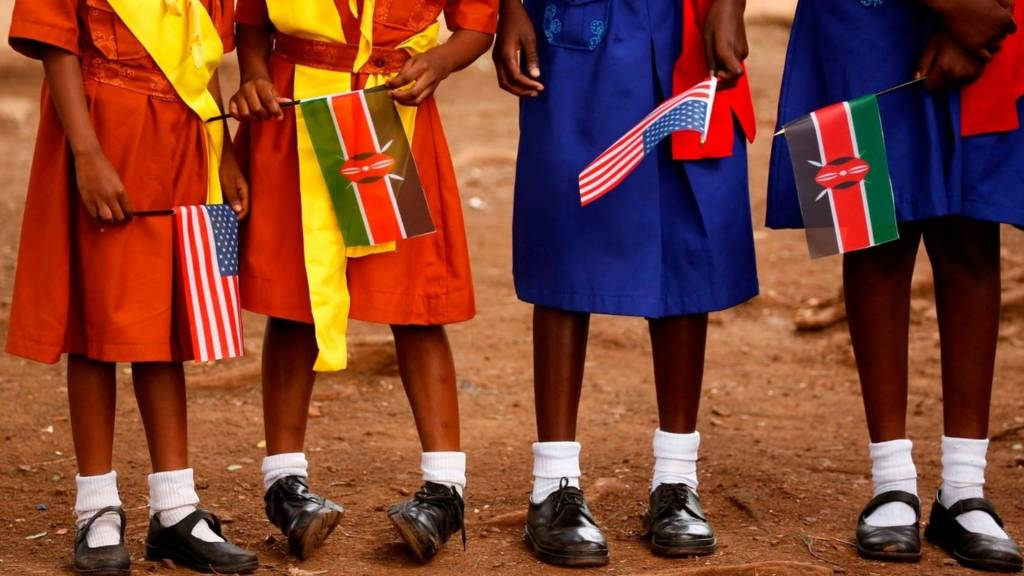 Girls hold Kenyan and US flags