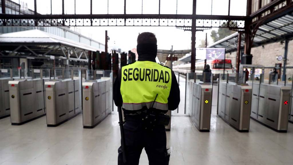 A private security agent stands guard at an empty station in Madrid