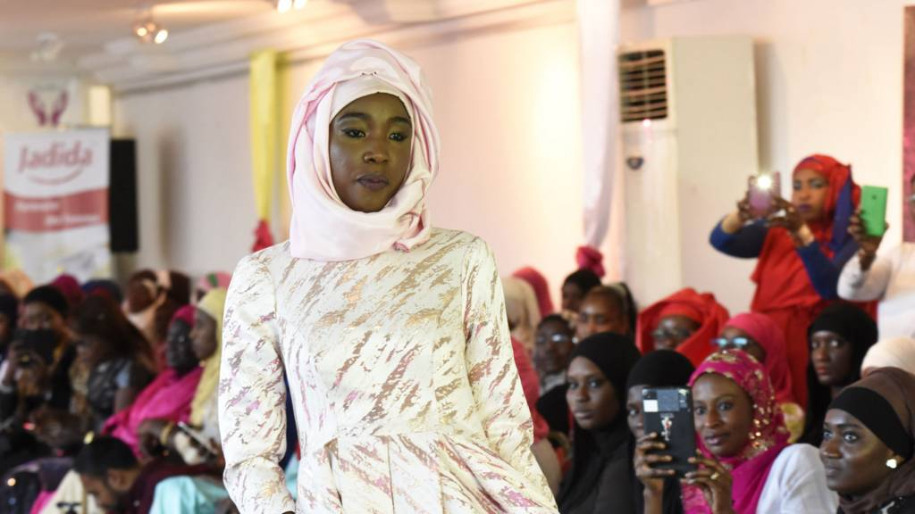 A model presents a hijab and a dress on 30 January 2016 during the Muslim Woman show in Dakar, on the eve of World Hijab Day