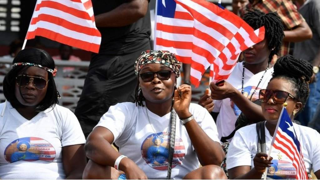 People hold Libearian flags as they attend a friendly football match between Weah All Stars, the team of Liberia's president-elect, and Armed Forces of Liberia team on January 20, 2018, in Monrovia, two days ahead of the presidential inauguration