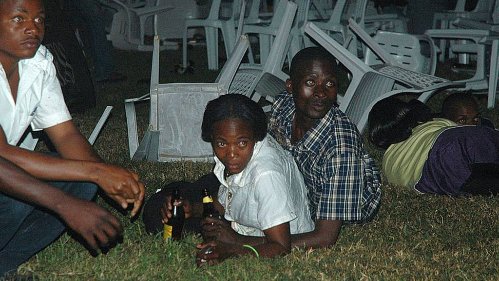 Survivors are seen at an Ethiopian-owned restaurant in the Kabalagala area of Kampala late on July 11, 2010 moments after twin bomb blasts tore through crowds of football fans watching the World Cup final, killing 64 people, including an American, and wounding scores others