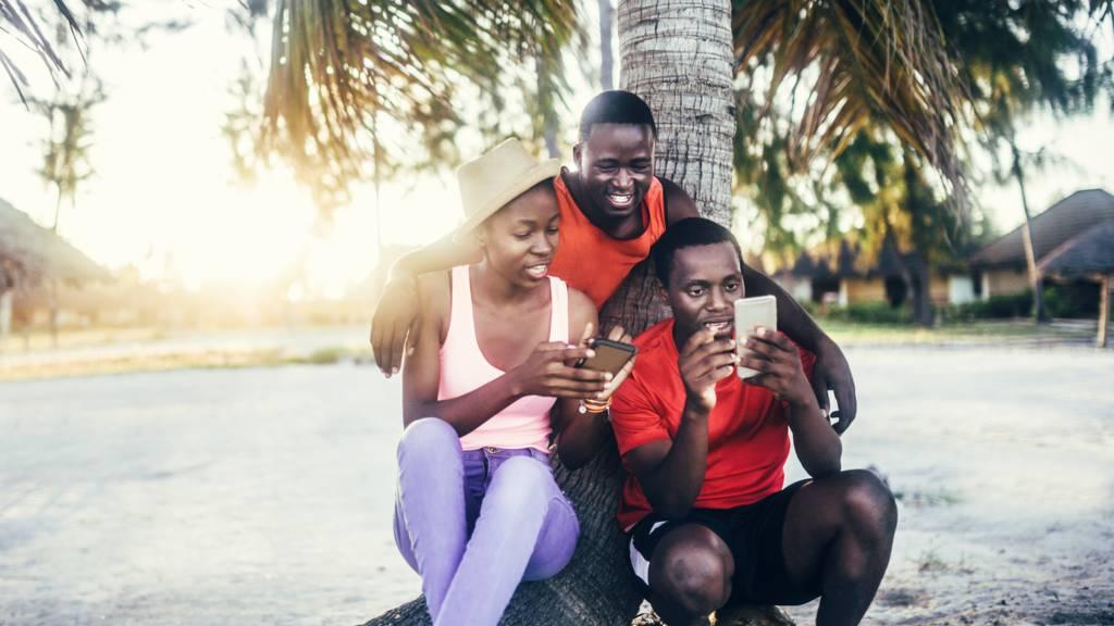 People looking at their phones under a tree in Zanzibar, Tanzania