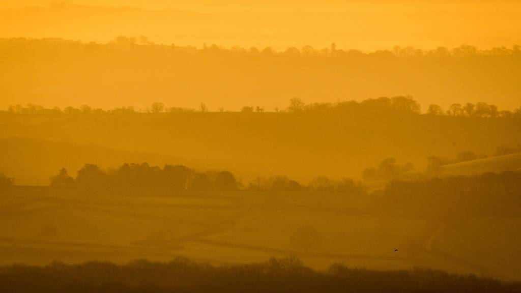 Tree lined ridges poke through the mist and fog as it hangs in valleys on the Mendip hills, Somerset at sunrise