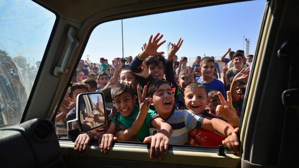 أطفال ينظرون في عربة عسكرية